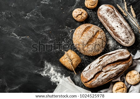 Bakery - gold rustic crusty loaves of bread and buns on black chalkboard background. Still life captured from above (top view, flat lay). Layout with free copy (text) space. #1024525978