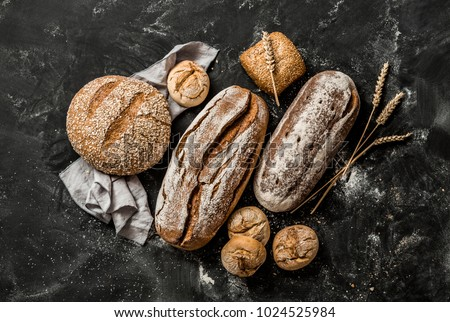Bakery - gold rustic crusty loaves of bread and buns on black chalkboard background. Still life captured from above (top view, flat lay). #1024525984