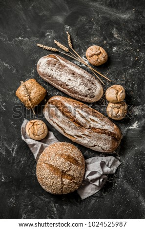 Bakery - gold rustic crusty loaves of bread and buns on black chalkboard background. Still life captured from above (top view, flat lay). #1024525987