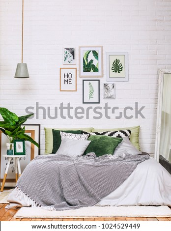 bedroom interior in gray green tones with pictures on a white wall