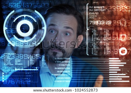 Unexpected results. Emotional smart programmer raising his eyebrows while looking at the information on his futuristic transparent screen and feeling surprised because of it #1024552873