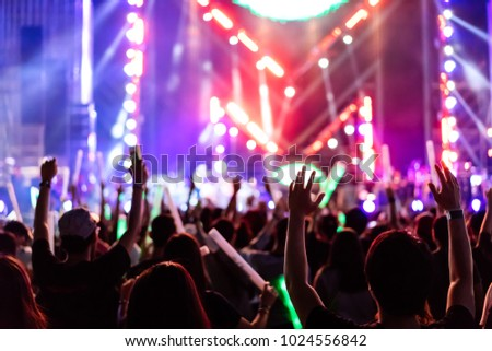 Crowd of hands up concert stage lights and people fan audience silhouette raising hands in the music festival rear view with spotlight glowing effect #1024556842