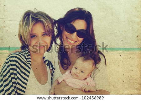 two beautiful girls with a baby on the beach. Photo in old color image style.