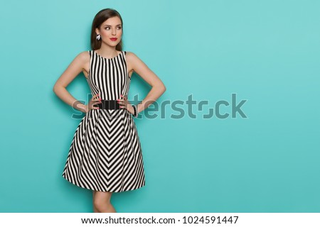 Charming fashion model in striped dress posing with hands on hip and looking away. Three quarter length studio shot on turquoise background. Royalty-Free Stock Photo #1024591447