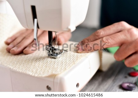 closeup of a young caucasian man sewing a beige fabric with a sewing machine #1024615486