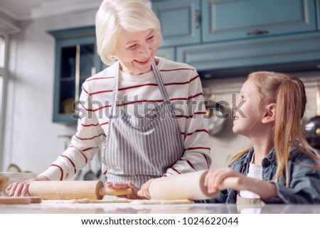 Important lesson. Happy senior woman in an apron explaining her little granddaughter how to roll out dough while smiling at her lovingly #1024622044