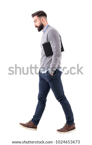 Thoughtful young businessman carrying notebook under the arm walking and looking down. Full body length portrait isolated on white studio background. #1024653673