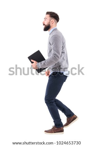 Side view of excited smart casual businessman running with notebook in hand. Full body length portrait isolated on white studio background. #1024653730
