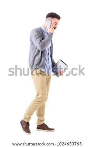 Business man talking on the phone walking and carrying tablet computer looking down. Full body length portrait isolated on white studio background. #1024653763