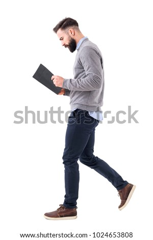 Profile view of young bearded businessman walking while reading notebook or planner. Full body length portrait isolated on white studio background. #1024653808