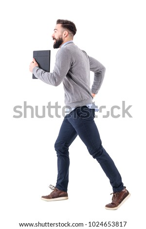 Profile view of young businessman with notebook running. Deadline concept. Full body length portrait isolated on white studio background. #1024653817