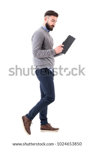 Relaxed smart casual businessman walking and reading notebook. Full body length portrait isolated on white studio background. #1024653850