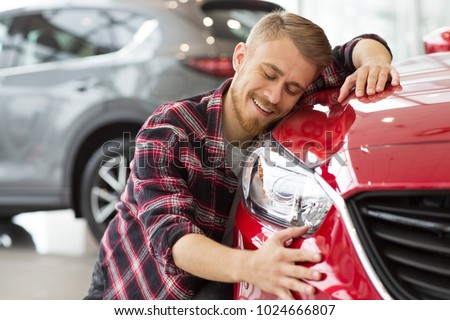 Shot of a handsome young happy bearded man embracing his new car at the dealership smiling joyfully with his eyes closed copyspace happiness love travelling vehicle automotive transport. #1024666807