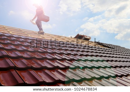 Tiling a roof Royalty-Free Stock Photo #1024678834