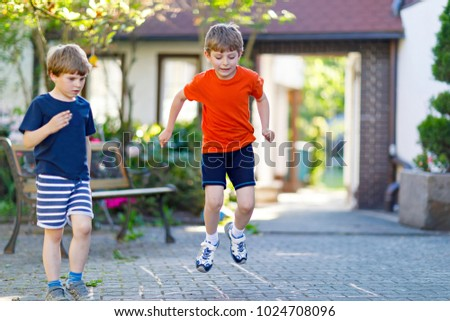 Two little school and preschool kids boys playing hopscotch on playground #1024708096