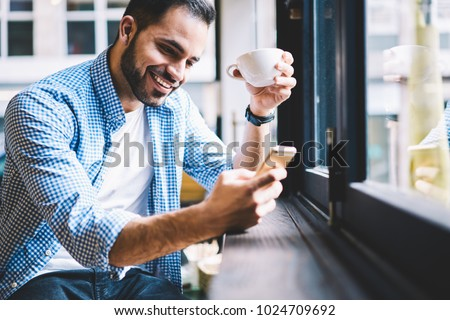 Cheerful male person happy to receive messages from friend checking mail via smartphone during rest in cafe, smiling man satisfied with getting good news using telephone fr networking drinking coffee Royalty-Free Stock Photo #1024709692