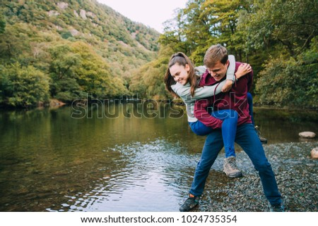 Teenage boy has his sister in a piggy back hold and is pretending to throw her in to a lake while they are out hiking.  #1024735354