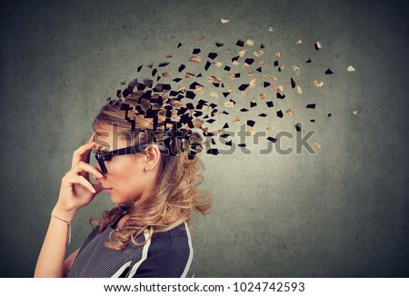Memory loss due to dementia or brain damage. Side profile of a woman losing parts of head as symbol of decreased mind function. #1024742593