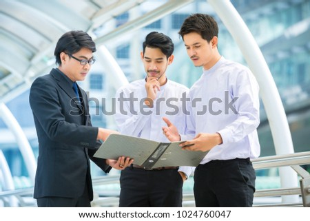 three male workers standing and discussion about work outside office,teamwork , workgroup concept #1024760047