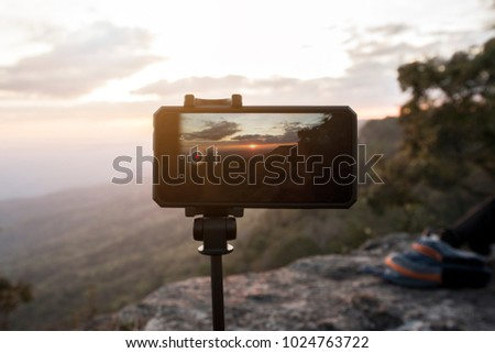 Mobile phone or smartphone on tripod with photography mode snapping a picture of sunset at the cliff : Time lapse taking sunset concept. Travel and holiday concept.