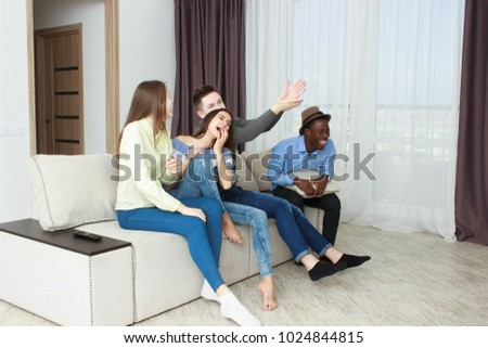 friends having fun together sitting on couch in living room #1024844815