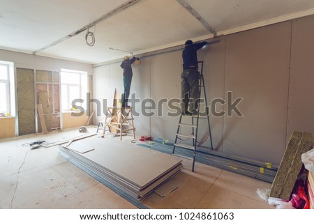Workers are installing plasterboard (drywall) for gypsum walls in apartment is under construction, remodeling, renovation, extension, restoration and reconstruction. #1024861063