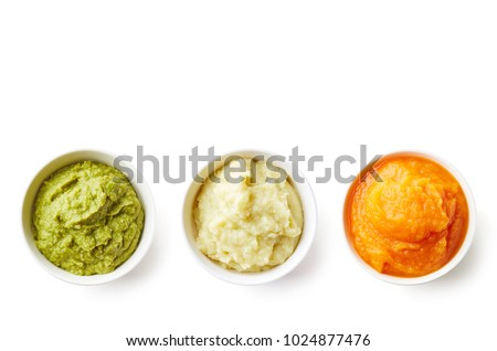Green, yellow and orange baby puree in bowl isolated on white background, top view #1024877476