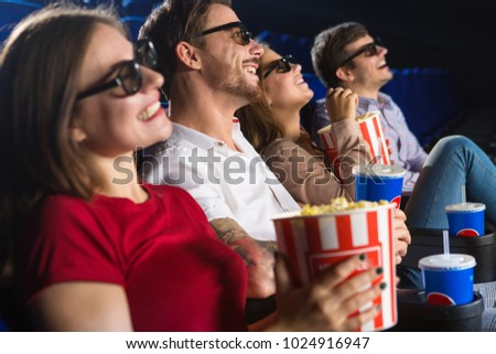 Group of friends smiling cheerfully watching a movie together at the cinema copyspace enjoyment recreation weekend leisure entertaining lifestyle friendship premiere spectators showtime. #1024916947