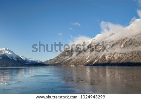 Fog clearning on a sunny winter day in the Lutak Inlet near Haines Alaska. #1024943299