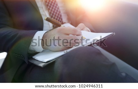 Businessman signs a contract. Holding pen in hand. #1024946311