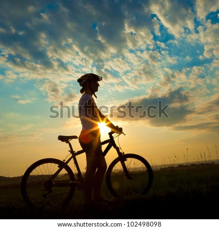 Biker-girl at the sunset on the meadow #102498098