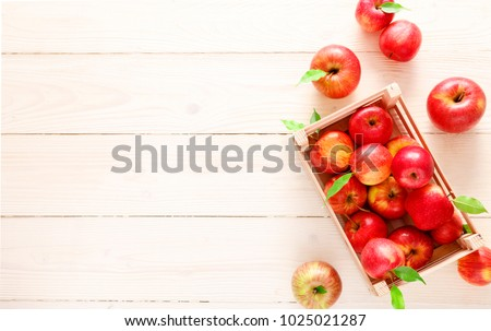 Red apples with green leaves on a white wooden surface and in a box top view #1025021287