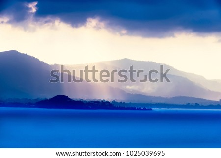 Sun rays passing through heavy storm clouds over the sea bay town. Wallpaper image. #1025039695