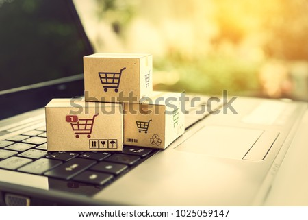 Online shopping / ecommerce and delivery service concept : Paper cartons with a shopping cart or trolley logo on a laptop keyboard, depicts customers order things from retailer sites via the internet. #1025059147