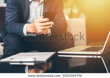 Handsome businessman in suit and eyeglasses speaking on the phone in office,Side view shot of a man's hands using smart phone in rear view of business man busy using cell phone at office. #1025064796