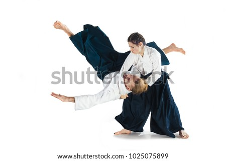 Man and woman fighting at Aikido training in martial arts school. Healthy lifestyle and sports concept. Man with beard in white kimono on white background. Karate woman with a concentrated face. Royalty-Free Stock Photo #1025075899