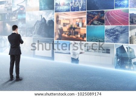 Thoughtful businessman looking at abstract digital photo gallery. Innnovation and art concept
