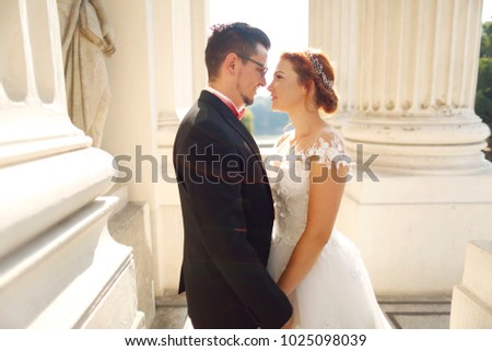 wedding couple posing in sun near old structure #1025098039