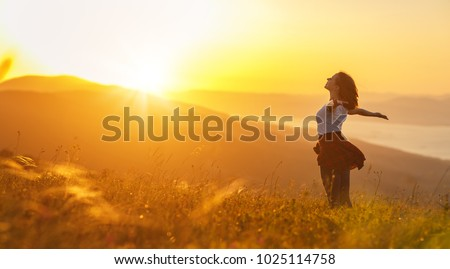 Happy woman   on the sunset in nature in summer with open hands Royalty-Free Stock Photo #1025114758