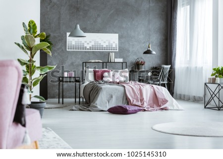 Feminine bedroom interior with pink sheets on gray bed and black, metal nightstands #1025145310