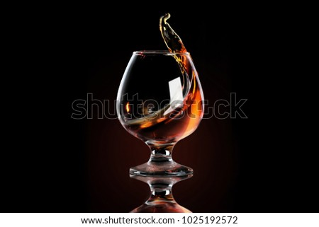 Splash of cognac in glass Royalty-Free Stock Photo #1025192572