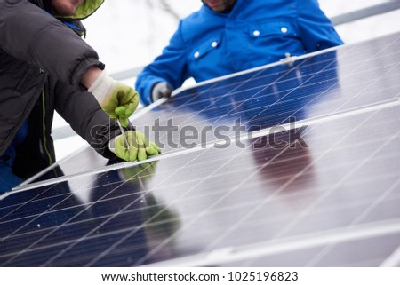 Cropped shot of professional electricians working on solar power plant factory renewable energy electricity alternative source environment friendly green photovoltaic farm occupation modern technology #1025196823