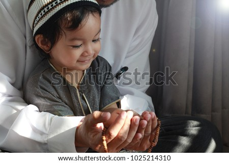 Religious Asian Muslim Man teaching his little son to pray to God with rosary at home.Sunset light shining through the window and touched boy body.Peaceful and Marvelous warm climate.Selective focus. #1025214310