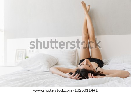 Portrait of a beautiful young woman lying on bed with legs up on bed at the bedroom #1025311441