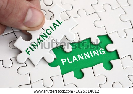 The human hand fills the last missing elements of the surface from the jigsaw puzzle. Image with words financial and planning #1025314012