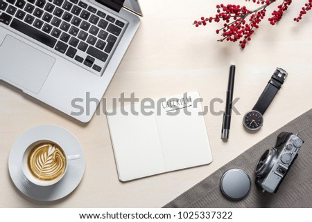 Checklist writing in open notepad with coffee mug, camera, clock and laptop lying on photography office desk with red berry plant as flat lay