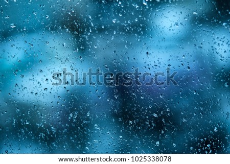 Raindrops on the windshield of the car in the early morning. Transparent glass after rain, cold abstract photo. Texture of glass with scattered rain drops and a blurry background in the late evening. #1025338078