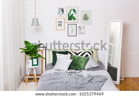 bedroom interior in gray green tones with a ficus mirror and pictures on a white wall