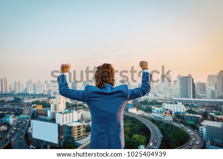 Successful Western businessman with hands up looking at the city at sunset #1025404939