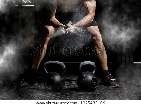 Weightlifter clapping hands and preparing for workout at a gym. Focus on dust #1025433106